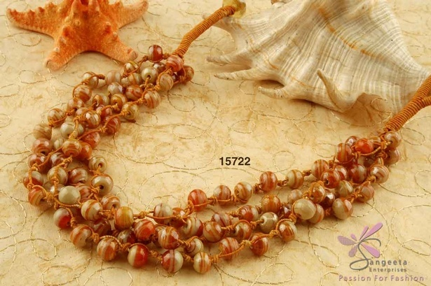 Necklace of four rows is in orange and beige lustre glass beads