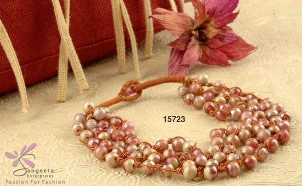 Necklace of four rows is in pink and beige colour glass beads